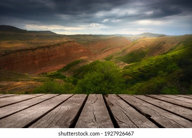 Beautiful background with misty mountains and empty wooden table in nature outdoor. Natural template landscape.