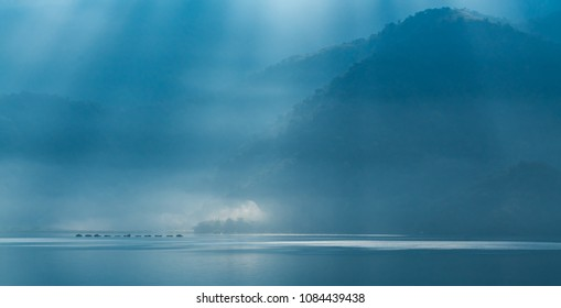 Beautiful Background in the morning with Clouds, Sunlight and sky reflect in the lake at Sun Moon Lake. Taiwan, Blue and Cool Tone Photography.