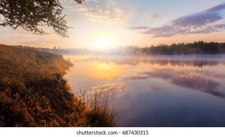 beautiful background of nature. wonderful misty landscape. amazing foggy morning, colorful sky reflected in the water of tranquil lake. picturesque dramatic scene.