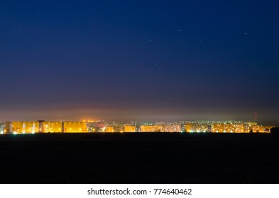 Beautiful background of night sky with stars and the lights of the big city homes summer