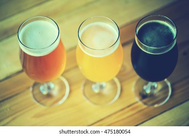 Beautiful background of the Oktoberfest. Glasses of cold fresh white, light and dark beer on the wooden bar counter in the pub. Assorted alcohol in a Flight Ready for Tasting. Blue toned