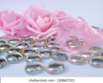Beautiful background with pink rose, decorative patterned bag and glass pebbles.