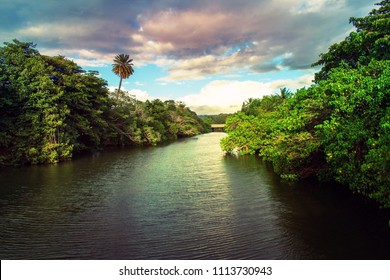 Beautiful background scenery with reflection of Anahulu water stream from sunlight by Rainbow bridge (Haleiwa) flows into the sea at golden hour in Haleiwa town , Northshore,Hawaii USA