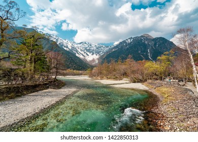 Beautiful Background Wallpaper of Crystal Clear Turquoise Color Azusa River along with Pine Trees and Snow Mountain Valley under Cloudy Blue Sky in Kamikochi. Tourist Destination in Nagano Japan