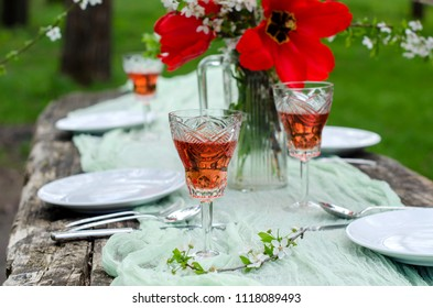 Beautiful background-festive table in the garden. Old wooden table. Cherry blossoms. Glasses of wine. Soft green runner. Selective focus. Blurred background.