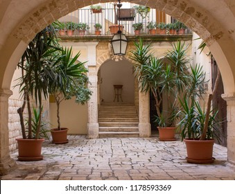 Beautiful backyard with arch, plants in pots, stairs and lantern. Patio decoration. Ancient courtyard background. Medieval architecture. Cozy italian backyard. Travel and architecture concept.