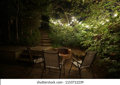 Beautiful backyard lighting strung through trees surrounded by patio furniture and a fire pit