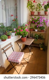 Beautiful balcony with small table, chair and flowers.