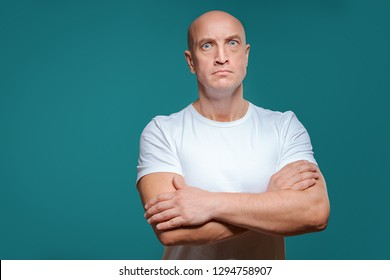 beautiful bald serious man in white t-shirt on blue background