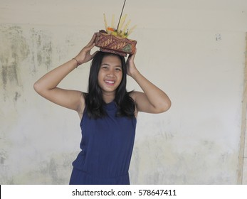 Beautiful Balinese teenager with blue dress and an offering basket on head