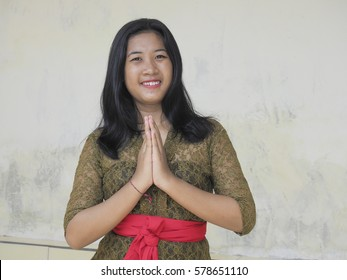 Beautiful Balinese teenager in traditional clothing with hands together in prayer Hindu