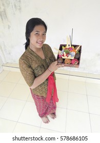 Beautiful Balinese teenager in traditional dress with offering basket in hands