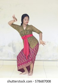 Beautiful Balinese teenager in traditional dress and traditional dance movement