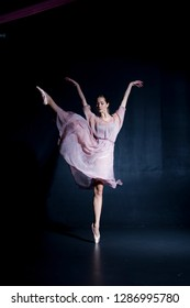 Beautiful ballerina in pointe and dress on a black background dancing