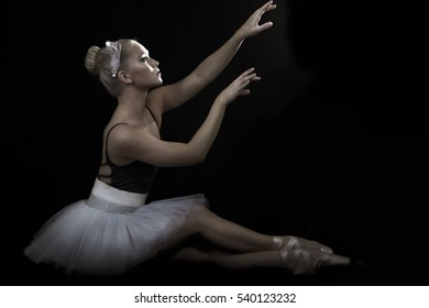 Beautiful ballerina in seated dance pose, in side view with light catching her face