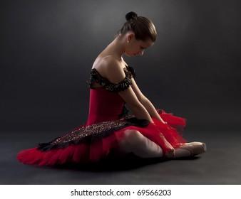 Beautiful ballerina wearing a red tutu on black background