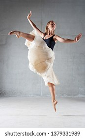 Beautiful ballet dancer jumping up with floating skirt on stage, indoors. Female ballerina conceptual power energy lightness, performing arts. Vigor performer artistic expression, choreography life.