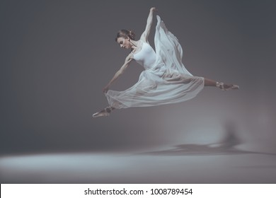 beautiful ballet dancer jumping in white dress - Shutterstock ID 1008789454
