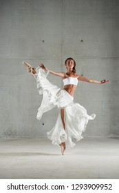 Beautiful ballet dancer lifting leg up with floating fabric skirt turning motion, conceptual balance, flexibility lightness, smiling on stage indoors. Artistic female doing pirouette, body work.