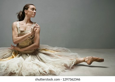 Beautiful ballet dancer on floor with tutu and point shoes stretching legs, conceptual romantic emotional expression, flexibility, stage indoors. Artistic female performer beauty body work, lifestyle.