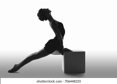 Beautiful ballet dancer posing in the Studio performing the deflection in the back and leaning on a big cube silhouette black and white