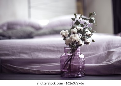 Beautiful banch of cotton in lilac glass vase in bedroom interior