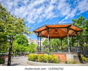 A beautiful bandstand with a wooden brown roof and a geometrical shape is the famous Chamberi square in Madrid the capittal of Spain, in Europe. The picture was taken in Summer, in a sunny morning.