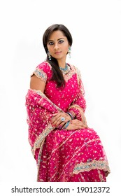 Beautiful Bangali bride in colorful dress sitting, isolated