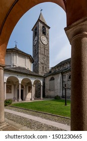 The beautiful baptistery and the bell tower of Baveno, Italy, framed by the columns of the portico of the via crucis, in the monumental complex
