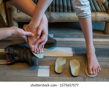 Beautiful bare children's feet with therapeutic orthopedic insoles for shoes on a wooden parquet background. Flatfoot treatment. Closeup of little male barefoot legs