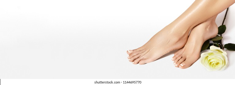 Beautiful bare Feet. Nail Varnishing, French Manicure in white color. Pedicure, Nails Polish in Beauty Salon Concept on white background