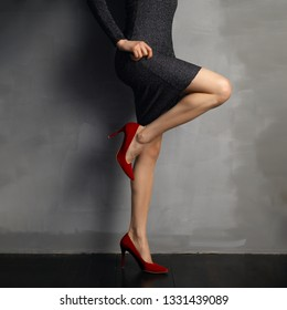 Beautiful bare female legs in red patent leather shoes, bent knee, view in profile.