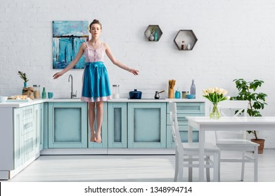 beautiful barefoot girl in apron levitating in air in kitchen