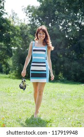 beautiful barefoot woman walking on lawn