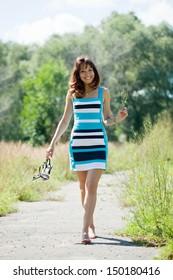 beautiful barefoot woman walking in summer park