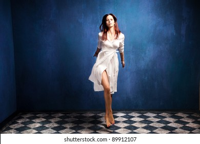 beautiful barefoot woman in white dress in motion in empty room