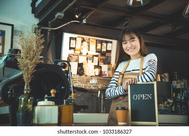 "Beautiful barista holding blackboard with word""open"" and smiles"