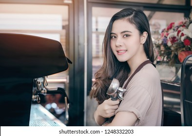 Beautiful barista smiling and holding porta filter while working at coffee shop.