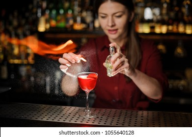 beautiful bartender girl adds peat whiskey to a red alcoholic cocktail in a crystal glass, spray it on a fire over a glass