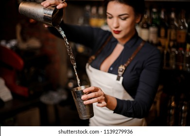 Beautiful bartender girl in the white apron transfusing drink from one steel cocktail shakers to another at the bar counter