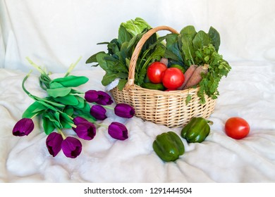 Beautiful basket of fresh vegetables on white background. Healthy vitamin products, Peking cabbage, carrots, tomatoes, greens and peppers.