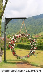 Beautiful basket swing of the wedding decorated with the colorful roses flower in the nature garden hanging on pole under tree branches.
