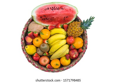 A beautiful basket of tropical fruits seen from above with pineapple, watermelon, bananas, clementines, papaya, strawberry, orange, peaches, kiwi and coconut