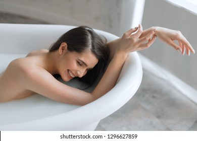 Beautiful bathing european brunette woman relaxing in milky bathtub, demonstrating her naked shoulder and arms