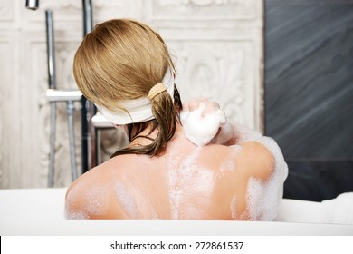 Beautiful bathing woman cleaning her back with soap.