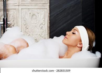 Beautiful bathing woman relaxing in bathtub.