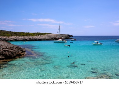 Beautiful bay at Cala Es Talaier, Minorca, Balearic Island, Spain. Boats sailing and people swimming in turquoise sea water. Perfect destination for summer family holidays.