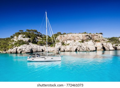 Beautiful bay in Mediterranean sea with sailing boat, Menorca island, Spain. Yachting, travel and active lifestyle concept