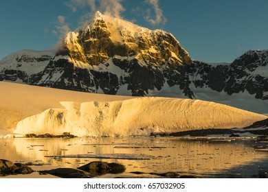 Beautiful bay with towering mountains in the background in Antarctica at sunset