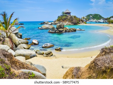 Beautiful bay with white sand beach, blue water and big boulders in Tayrona national park in Colombia with soft focus